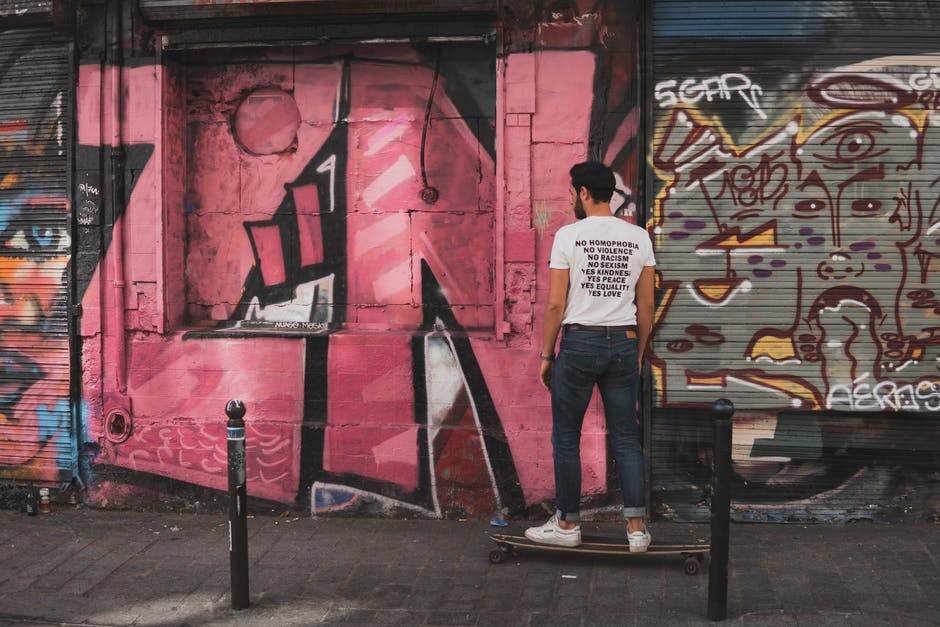 A person standing in front of a graffiti covered wall