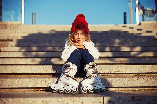 A little girl sitting on a wooden bench