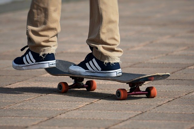 A pair of legs and feet on a skateboard